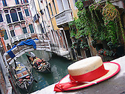 A gondolier's hat sits on a bridge as a gondola passes by in a Venice canal. Venice, Italy