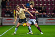 Sam Cosgrove (#16) of Aberdeen FC shields the ball from Craig Halkett (#26) of Heart of Midlothian FC during the Betfred Scottish Football League Cup quarter final match between Heart of Midlothian FC and Aberdeen FC at Tynecastle Stadium, Edinburgh, Scotland on 25 September 2019.