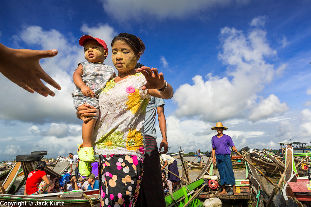 13 JUNE 2013 - YANGON, MYANMAR:   A man helps a woman and her child get off a boat at the Aung Mingalar Jetty in Yangon. The jetty is a stop for commuters who live on the far side of the Irrawaddy River and ride small boats back and forth across the river. Yangon, formerly Rangoon, is Myanmar's commercial capital and used to be the national capital. The city is on the Irrawaddy River and has a vibrant riverfront.  PHOTO BY JACK KURTZ