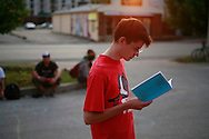 A young man reads a pamphlet being given away during the 2006 Plan-it-X Festival in Bloomington, Indiana. ..