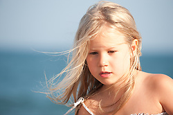 little girl with blonde hair at the beach