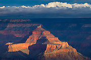 A small hole in the clouds on a stormy fall afternoon allows the sun to light up Vishnu Temple while the rest of the Grand Canyon is in a deep shadow. Vishnu Temple is visible from the south rim of the Grand Canyon National Park, Arizona.