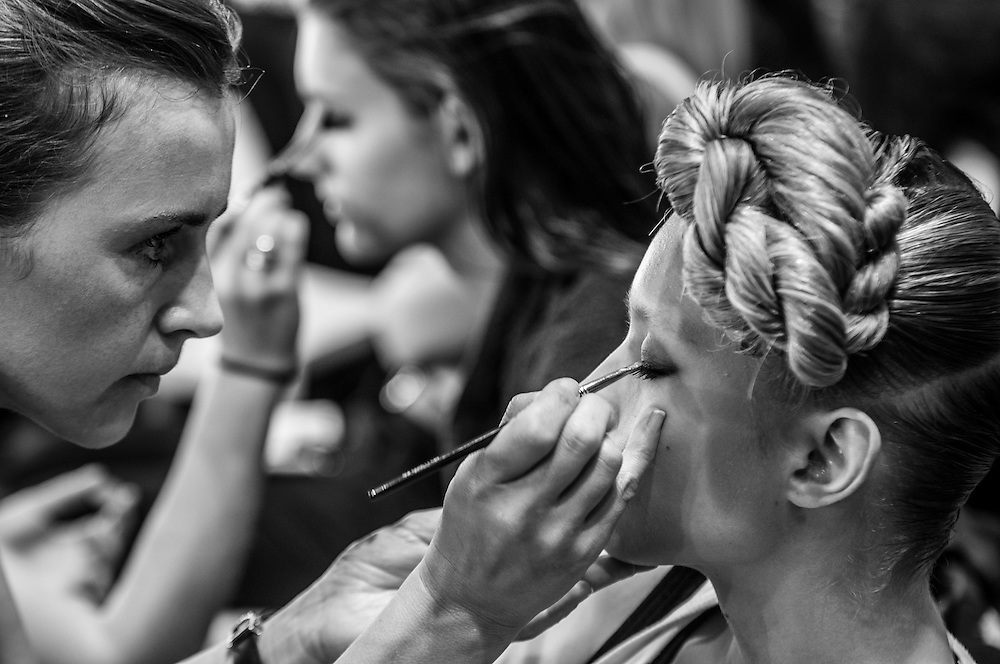 Models getting make-up touch-ups ahead of the next runway show in Somerset House, London.