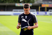 AFC Wimbledon goalkeeper Joe McDonnell (24) reading program before the game during the EFL Sky Bet League 1 match between AFC Wimbledon and Doncaster Rovers at the Cherry Red Records Stadium, Kingston, England on 26 August 2017. Photo by Matthew Redman.
