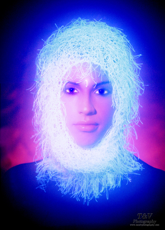 Portrait of a young woman with a glowing headpiece.Black light