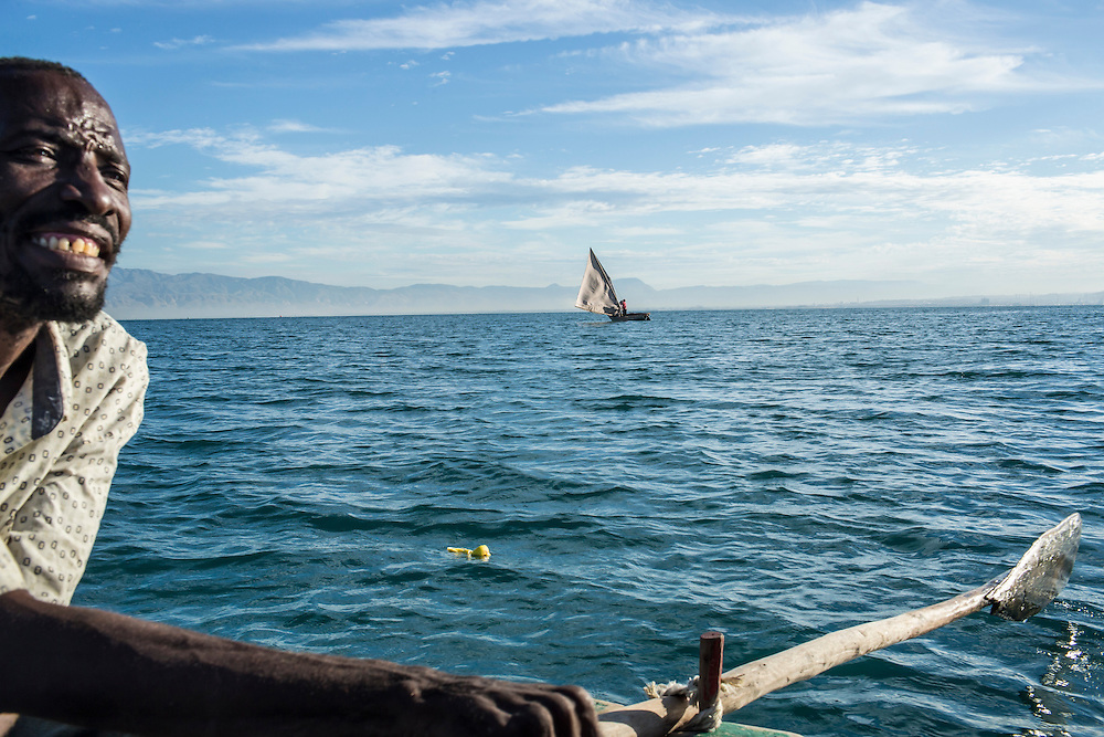 Fisherman Jean Claude Joseph rows a boat as his colleague checks nets on Monday, December 15, 2014 in Port-au-Prince, Haiti.