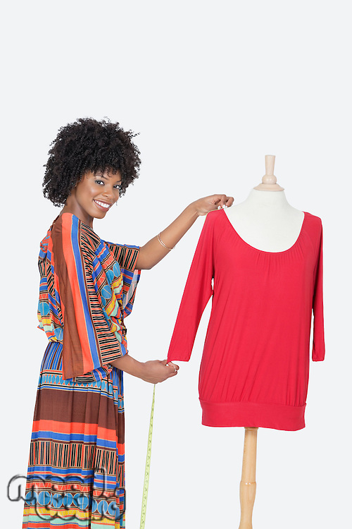 Portrait of African American female designer measuring a red tunic over gray background