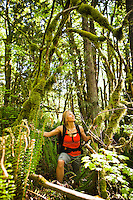 A woman with a backpack looking up at moss covered branches in a forest, Little Si trail, Washington, USA.