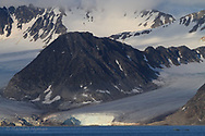 Glaciers flowing from mountains join at sea  in Smeerenburgfjorden on the north coast of Spitsbergen island; Svalbard, Norway.