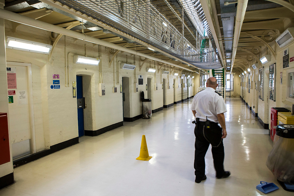 Officers walking to the main office. The ground floor central walkway of Benbow wing inside HMP/YOI Portland, a resettlement prison with a capacity for 530 prisoners. Dorset, United Kingdom.