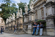 Visitors stand beneath the statues of twelve apostle outside the church St. Peter and St. Paul Church on Grodzka street, on 23rd September 2019, in Krakow, Malopolska, Poland.