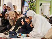 06 JULY 2016 - BANGKOK, THAILAND:  A family uses a tablet computer to record video before Eid services at Ton Son Mosque in the Thonburi section of Bangkok. Eid al-Fitr is also called Feast of Breaking the Fast, the Sugar Feast, Bayram (Bajram), the Sweet Festival or Hari Raya Puasa and the Lesser Eid. It is an important Muslim religious holiday that marks the end of Ramadan, the Islamic holy month of fasting. Muslims are not allowed to fast on Eid. The holiday celebrates the conclusion of the 29 or 30 days of dawn-to-sunset fasting Muslims do during the month of Ramadan. Islam is the second largest religion in Thailand. Government sources say about 5% of Thais are Muslim, many in the Muslim community say the number is closer to 10%.       PHOTO BY JACK KURTZ