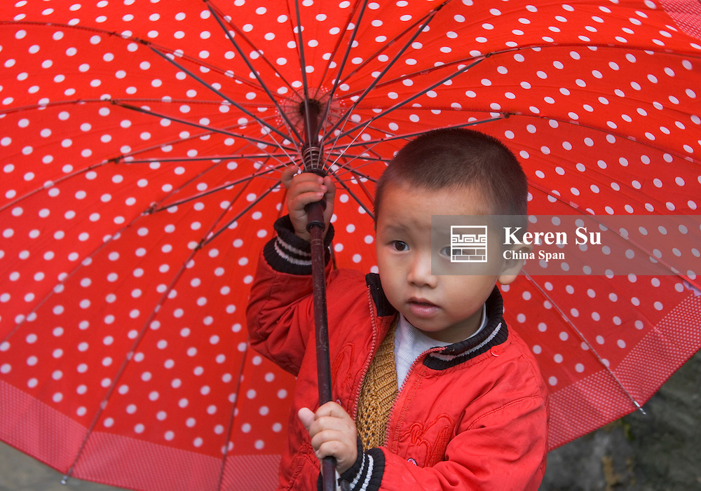 Boy with red umbrella in the old town, Guizhou, China
