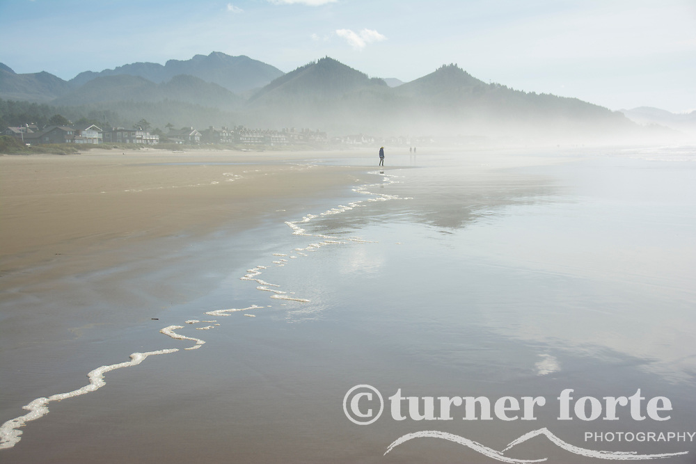 Adult silhouette explores the foggy shoreline of Cannon Beach, Oregon.