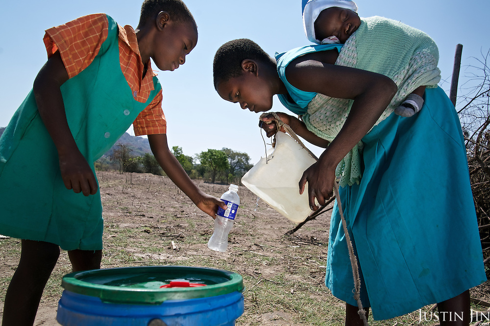 Liliosa, 16, helps another child to fill her bottle with water in Masvingo Province, Zimbabwe. Liliosa takes care of herself, her eight-month-old baby and her young sister, who is born HIV positive. <br /> <br /> Drought in southern Africa is devastating communities in Zimbabwe, leaving 4 million people urgently in need of food aid. The government declared a state of emergency,. <br /> <br /> Here in Masvingo Province, the country's hardest hit province, vegetation has wilted, livestock is dying, and people are at serious risk of famine. <br /> <br /> Pictures shot by Justin Jin