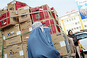 Two women (left) dressed in traditional burka dresses are walking past a cart carrying brand new television sets along a more modern Afghan woman and her young daughter, (right) on the streets of Kabul, Afghanistan.
