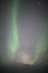 The northern lights glow over the sky at Bettles, Alaska.