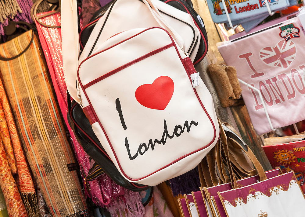 A bag with an emblem stating 'I Love London' hanging amongst lots of other memorabilia on a stall in central London