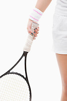 Midsection of a young Asian woman holding tennis racket over white background