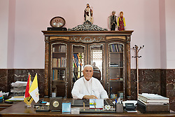 © Licensed to London News Pictures. Hamdaniyah, Iraq. 25/07/2014. Hamdaniyah, Iraq. A portrait of Yohanna Petros Mouche, the Syrian Catholic Archbishop of Mosul, sitting at his desk in the Christian academy in the Iraqi town of Hamdaniyah. Located close to the front line with the Islamic State, the relatively peaceful predominantly Christian town has seen over 600 Christian families arrive from nearby Mosul, with many crammed into unfinished houses.<br /> <br /> Having taken over Mosul Iraq's second largest city in June 2014, fighter of the Islamic State (formerly known as ISIS) have systematically expelled the cities Christian population. Despite having been present in the city for more than 1600 years, Christians in the city were given just days to either convert to Islam, pay a tax for being Christian or leave; many of those that left were also robbed at gunpoint as they passed through Islamic State checkpoints.. Photo credit : Matt Cetti-Roberts/LNP