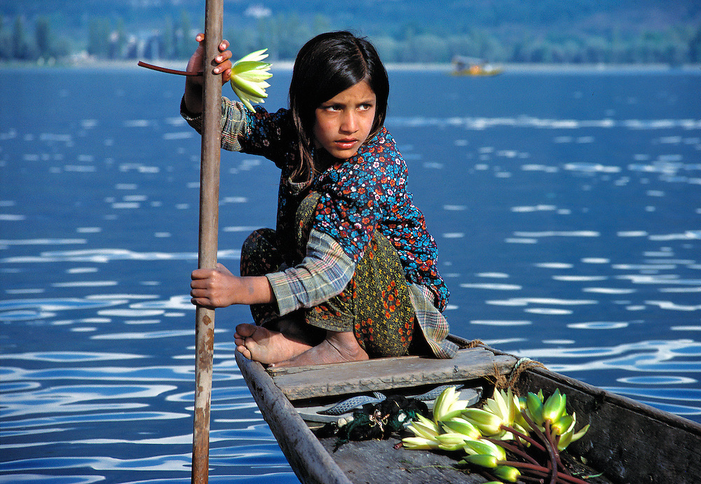 A young girl paddles a boat filled with lotus blossoms on Lake Dal, Srinagar, Kashmir, India.
