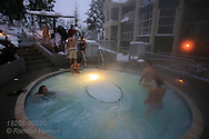Couple enjoys apres ski soak in hot springs pool at condo resort on Blackcomb Mountain; Whistler, British Columbia, Canada