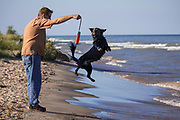 Mike Roemer plays with his dog Chica along the shore of lake Michigan near Two River, Wisconsin.