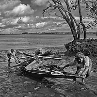 A fisherman and his family anchoring his boat after fishing in the Sundarbans, Bangladesh.<br /> Sundarbans, the largest delta on the planet earth is famous for its marine and estuarine fish resources. A large population is dependent on fishery activity and capture fisheries is treated as the backbone of Sundarban economy.