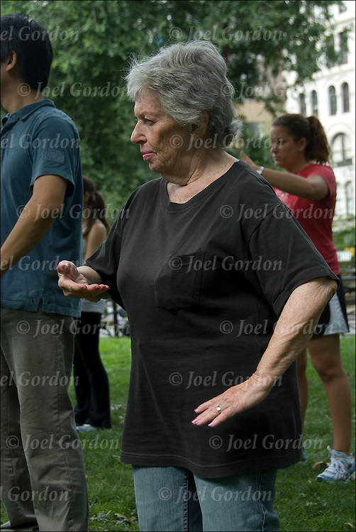 73 year old woman in group doing Tai Chi. Tai chi chuan is an internal Chinese martial art often practiced for health reasons. Tai chi is typically practiced for a variety of other personal reasons: its hard and soft martial art technique, demonstration competitions, health and longevity. This slow motion routine is being practice in groups of people in Union Square Park, NYC.