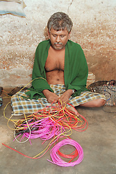 Indian man affected by muscular dystrophy; member of selfhelp group supported by charity ADD India; weaving basket using coloured threads,