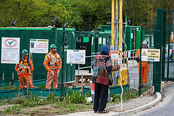 Harefield, UK. 27th April 2019. An environmental activist from Colne Valley Action speaks to security guards at osne of several entrances to a large area of land in Colne Valley which is being cleared of trees for the HS2 project. The Colne Valley is an area of natural beauty and large numbers of trees have been felled in recent weeks.