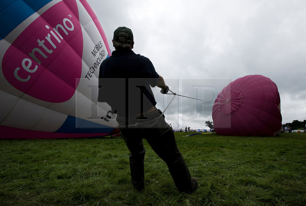 © Licensed to London News Pictures. 13/08/2011. Bristol, England. The 33rd Bristol International Balloon Fiesta was in full swing on Saturday evening - designated Party Night - thousands of people flocked to Ashton Court Estate to watch the spectacular Mass Ascent where some 85 balloons took to the cloudy evening skies...Following this a Night Glow event brought many of the balloons back into the main arena to fire their propane burners in time to a wide selection of music from over the past 40 years.  Photo credit : Ian Forsyth/LNP