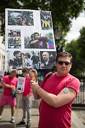 "© Licensed to London News Pictures . 10/08/2013 . London , UK . A protester with a placard with images of violence against gay people overlaid with the logos of Sochi Olympic Games sponsors , which are due to be held in Russia in 2014 . Demonstration against homophobic laws being enacted in Russia on Whitehall this afternoon (10th August 2013) . Legislation includes banning gay pride events for100 years , banning the distribution of "" propaganda of non-traditional sexual relations "" to minors , making it illegal for the adoption of Russian children by gay couples or any single person who comes from a country that recognises marriage equality and giving authorities the rights to arrest foreign nationals whom they suspect are LGBT or pro gay with the right to detain them for up to 14 days. Photo credit : Joel Goodman/LNP"