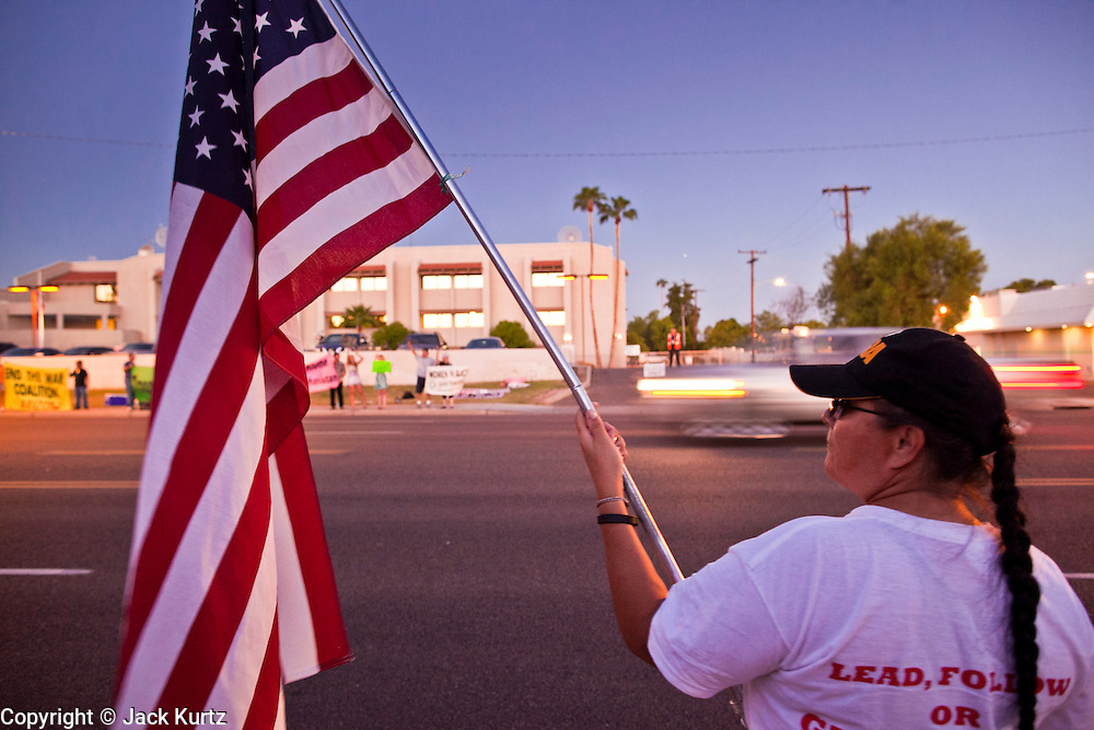 26 SEPTEMBER 2010 - PHOENIX, AZ: A woman holds an American flag during a demonstration against Sen John McCain in Phoenix Sunday. About 200 people demonstrated and picketed against Arizona Republican Senator John McCain at the studios of KTVK TV in Phoenix, Sunday, Sept 26. They picketed the TV station because McCain was debating his opponents there. They were demonstrating against McCain's positions on the war in Afghanistan, Don't Ask Don't Tell (Gays in the military) and the DREAM Act (for immigrant rights). PHOTO BY JACK KURTZ