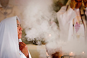 24 APRIL 2005 - SAN CRISTOBAL DE LAS CASAS, CHIAPAS, MEXICO:  A Mayan Indian woman carries incense into a small Catholic church in San Cristobal de las Casas, Chiapas. The Catholic church in Chiapas is under increasing pressure and facing competition from evangelical Protestant churches in Mexico. PHOTO BY JACK KURTZ