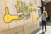 A woman reads the message left on a shop on King Street in the historic district in preparation for Hurricane Irma September 8, 2017 in Charleston, South Carolina. Imra is expected to spare the Charleston area but hurricane preparations continue as Irma leaves a path of destruction across the Caribbean.