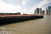 Brooklyn Pier 1 being taken down with Manhattan waterfront in the background