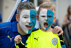 © Licensed to London News Pictures. 07/05/2016. Leicester, UK. Leicester City fans celebrating outside the King Power stadium before their match with Everton before lifting the Premiership trophy. Pictured, a fan and his son painted their faces in foxes colours. Photo credit: Dave Warren/LNP