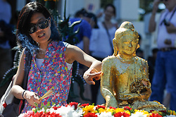© Licensed to London News Pictures. 09/04/2017. London, UK.  Worshippers and visitors attend the Thai New Year festival of Songkran at The Buddhapadipa Temple in Wimbledon.  Traditionally, the sprinkling of water symbolises the washing away of the past, and water would have been gently poured onto elders, or images of Buddha.