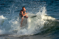 """Surfer Reacts as He is Hit by a Wave at """"Surf City USA"""", Huntington Beach, California"""