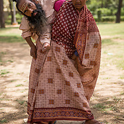 NEW DELHI, INDIA- APRIL, 27, 2017: Baby, 45, pictured holding Anuj Mandal, 65, on her back in a park in New Delhi, India.<br />