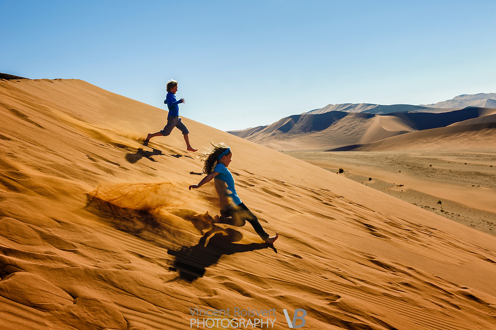 Two kids running down Sossusvlei dunes in Namib-Naukluft Park, Namibia