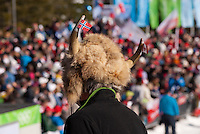 A man wears a traditional horned hat adorned with Norwegian and Canadian flags at the 2010 Olympic Winter Games in Whistler, BC Canada