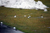 Golf balls rest alongside the practice green where a pile of snow slowly melts away under rainfall Wednesday at Prairie Falls Golf Course.