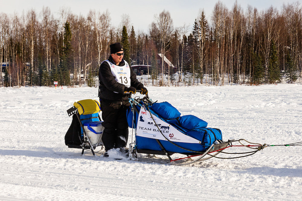 Musher John Baker competing in the 41st Iditarod Trail Sled Dog Race on Long Lake after leaving the Willow Lake area at the restart in Southcentral Alaska.  Afternoon.