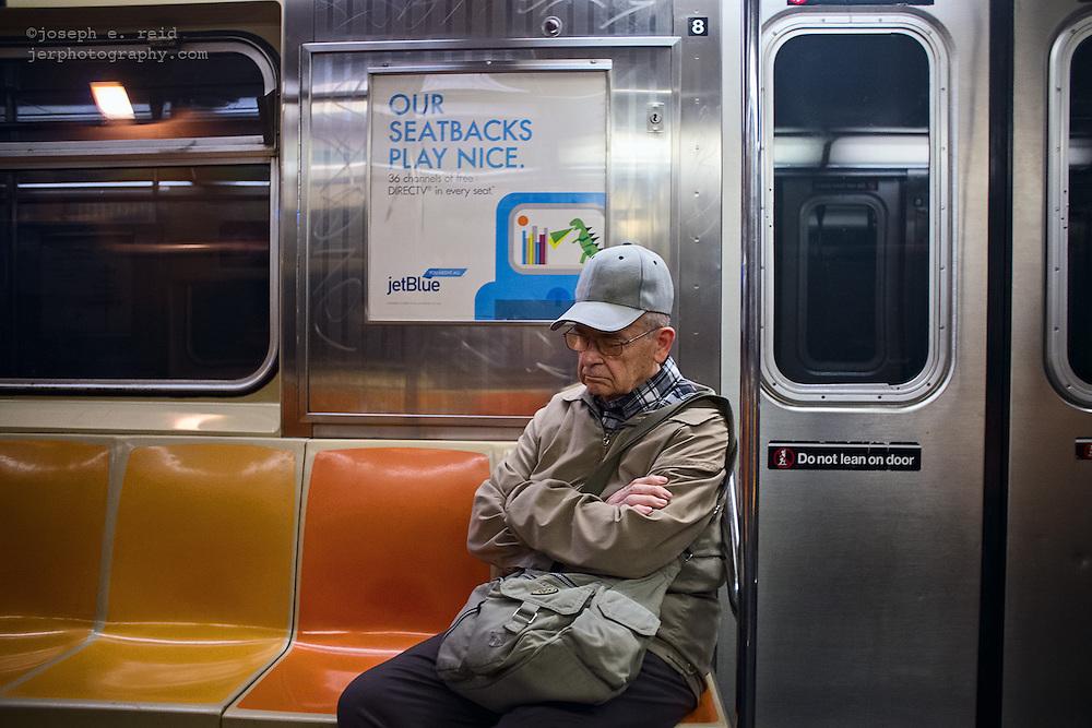 Man in beige sleeping on subway