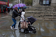 A family visiting the capital endures heavy rainfall on an autumn afternoon outside St. Martin-in-the-Fields church on Trafalgar Square, on 24th October 2019, in Westminster, London, England.