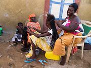 Een vrouw vlecht de haren van een meisje. De wijk Guédiawaye in Dakar. De wijk is in 2005 zwaar getroffen door overstromingen, waarbij veel huizen zijn verdwenen. De gevolgen hebben nog altijd een forse impact op het leven daar. Er is nog altijd geen goede irrigatie en de gezondheid lijdt onder de vervuiling.