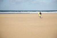 Surfer carrying surfboard walking on beach back view