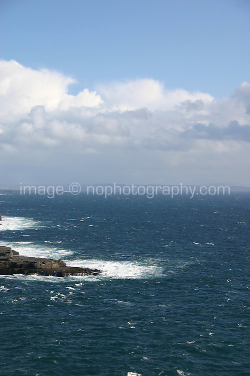 View from cliffs at Dun Aonghus fort, Inis Mor the Aran Islands, Connemara, County Galway, Ireland. Landscape with rough atlantic sea, blue sky